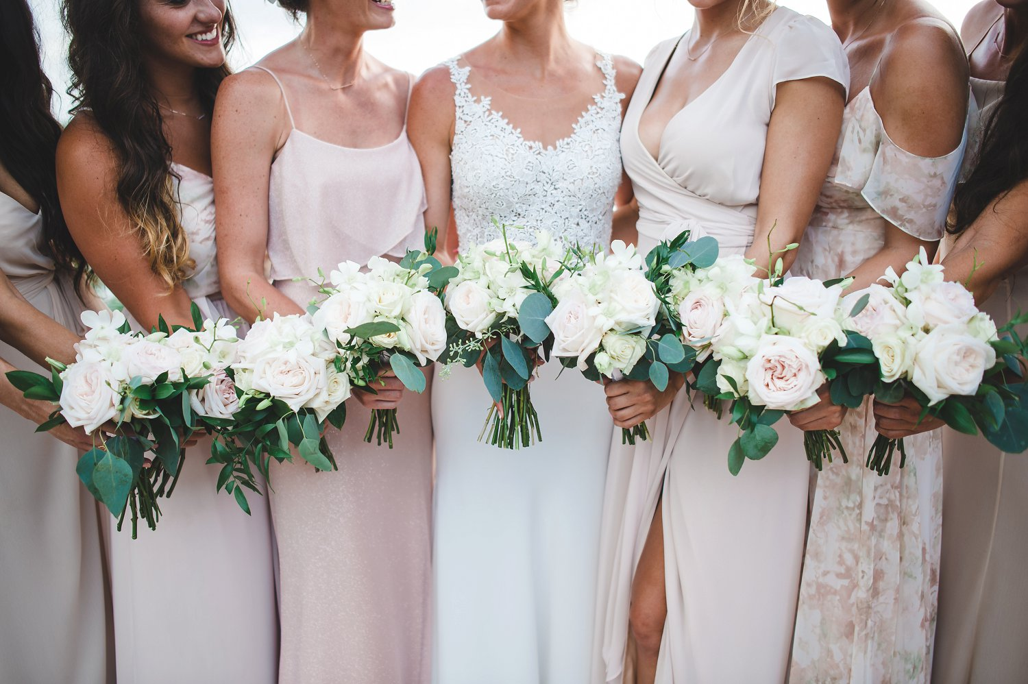 Blush roses and white orchid bouquets with blush and neutral mismatched bridesmaids dressed.