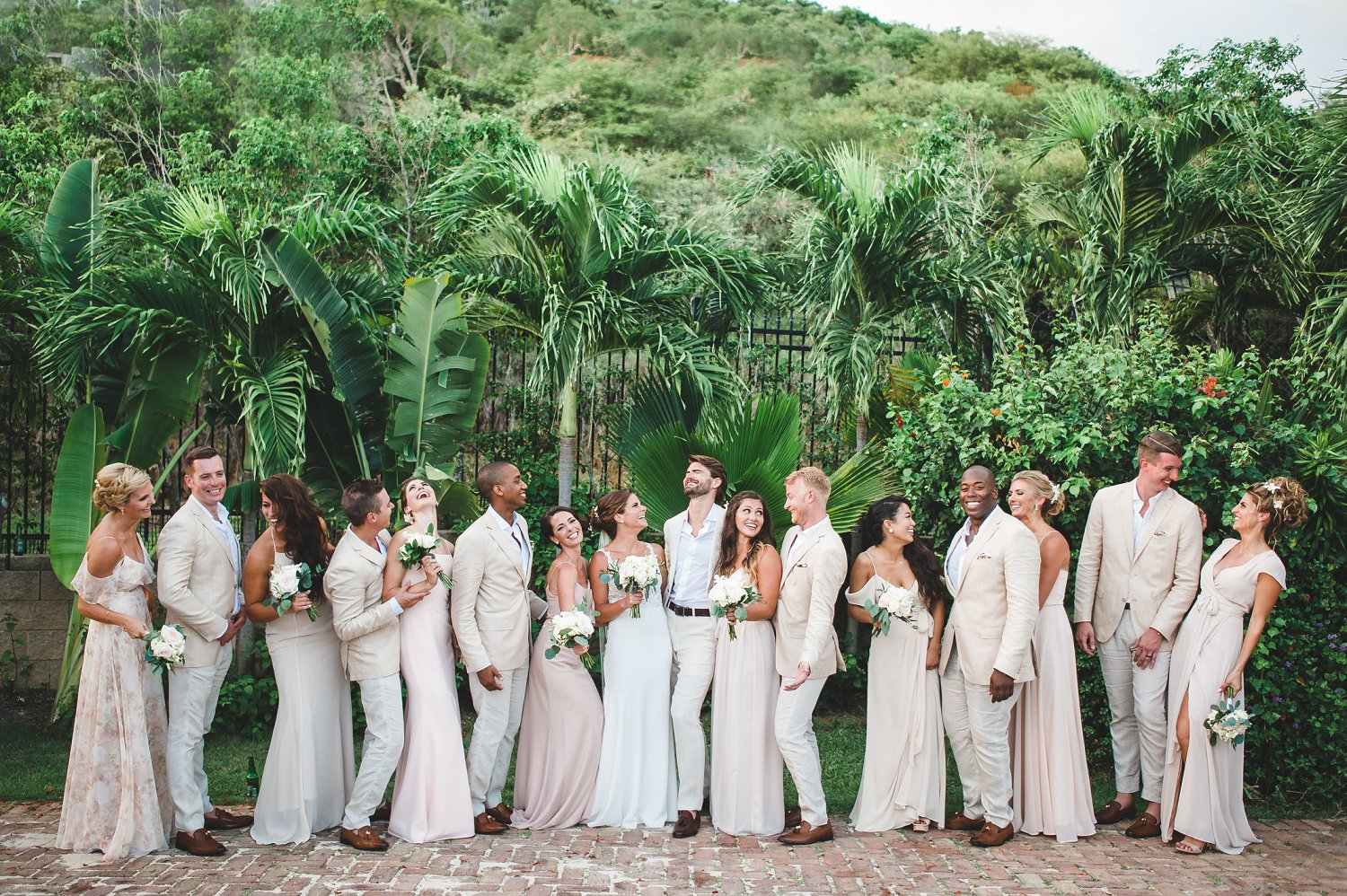 Wedding party (bride, groom, bridesmaids, and groomsmen) portrait with neutral mismatched dresses and tan/khaki suits