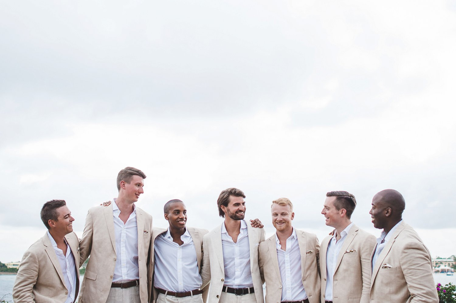 Groom and groomsmen in tan/khaki suits and white shirts with no tie waiting for destination wedding ceremony.