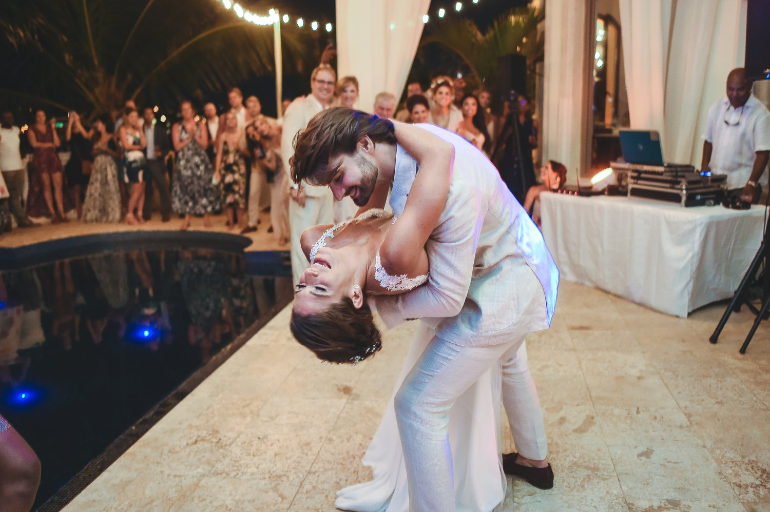 Groom dips bride during first dance beside pool at destination wedding.