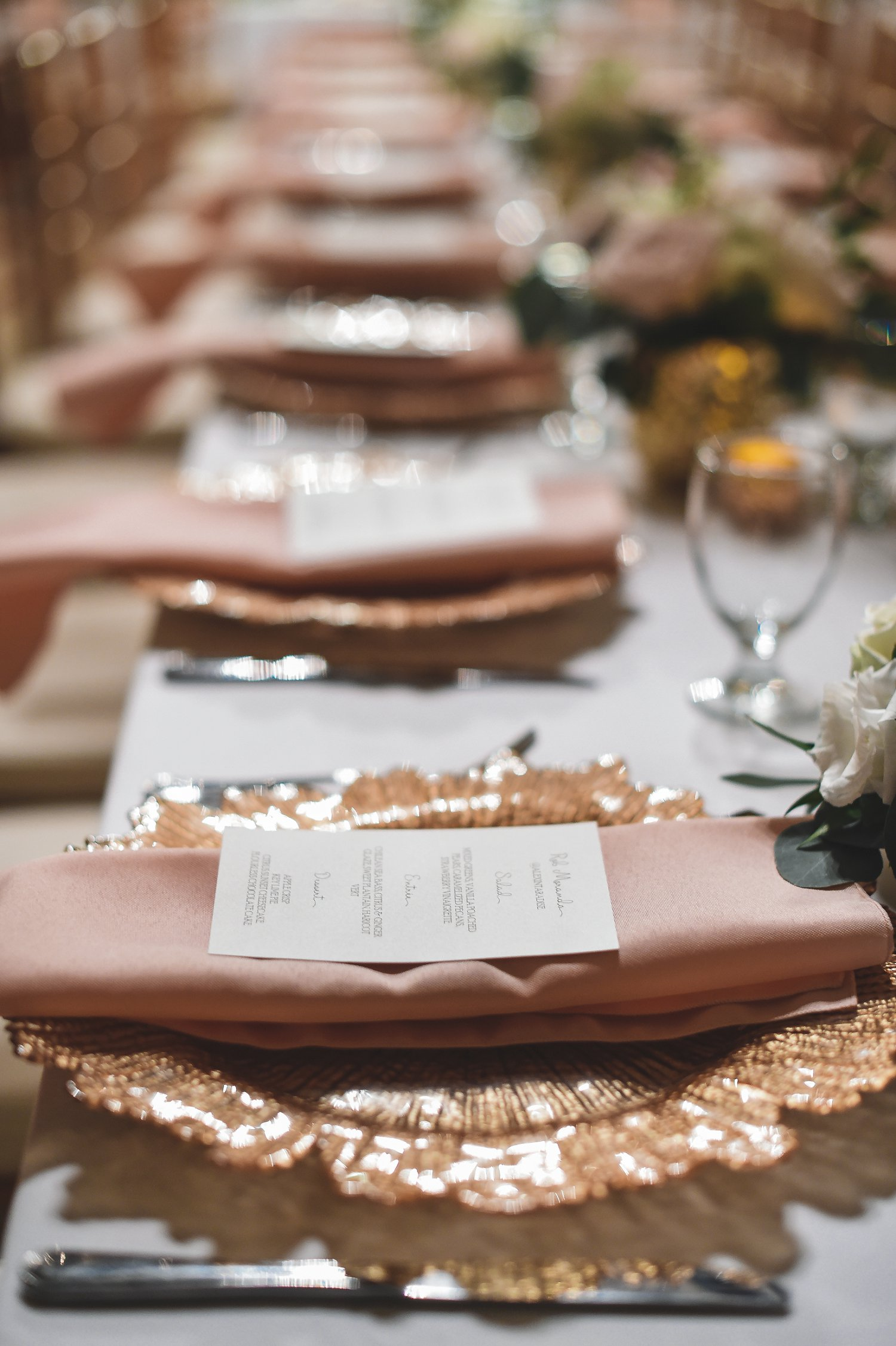 Destination wedding reception with blush napkins and gold chargers.