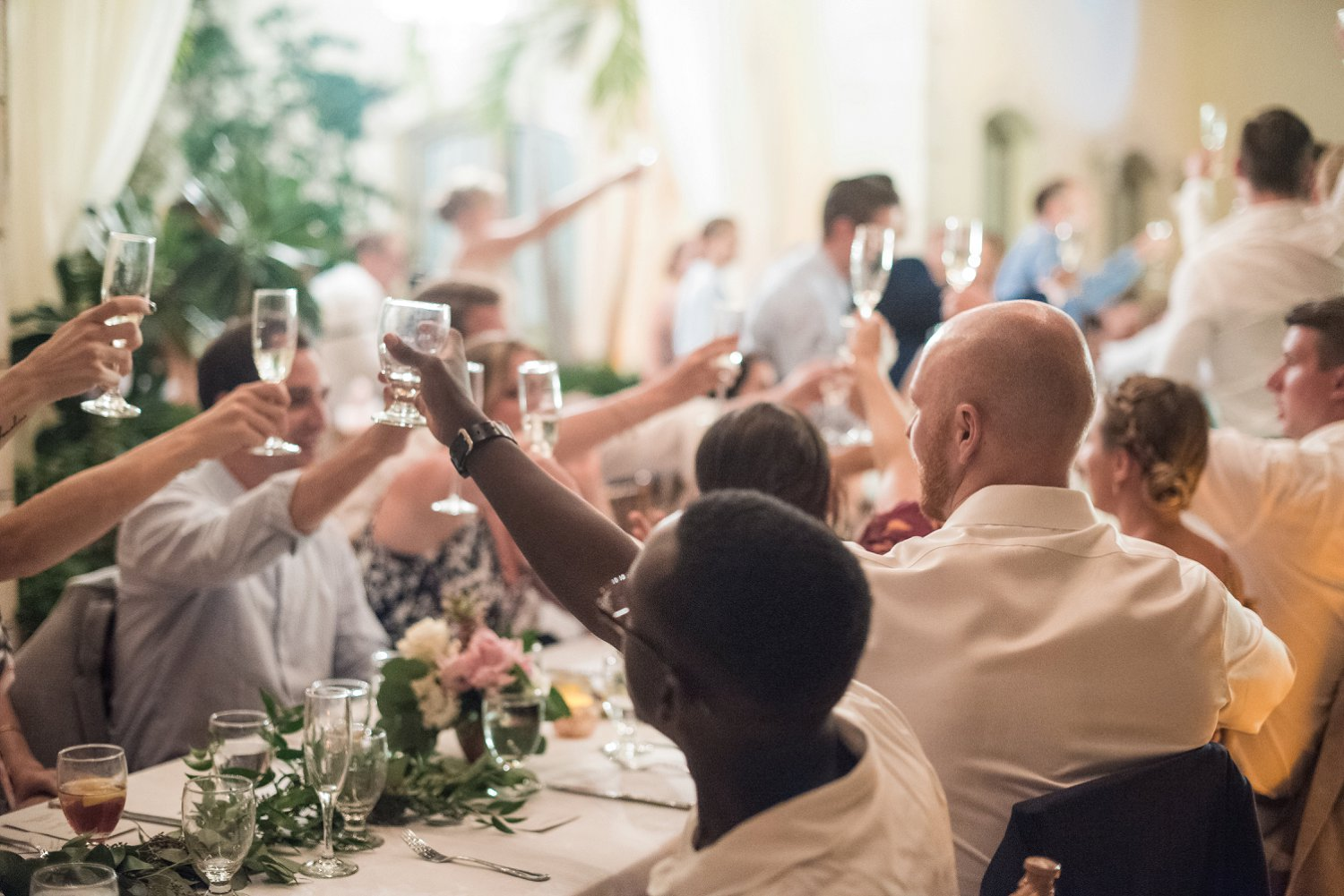 Wedding guests toast the bride and groom at dinner.