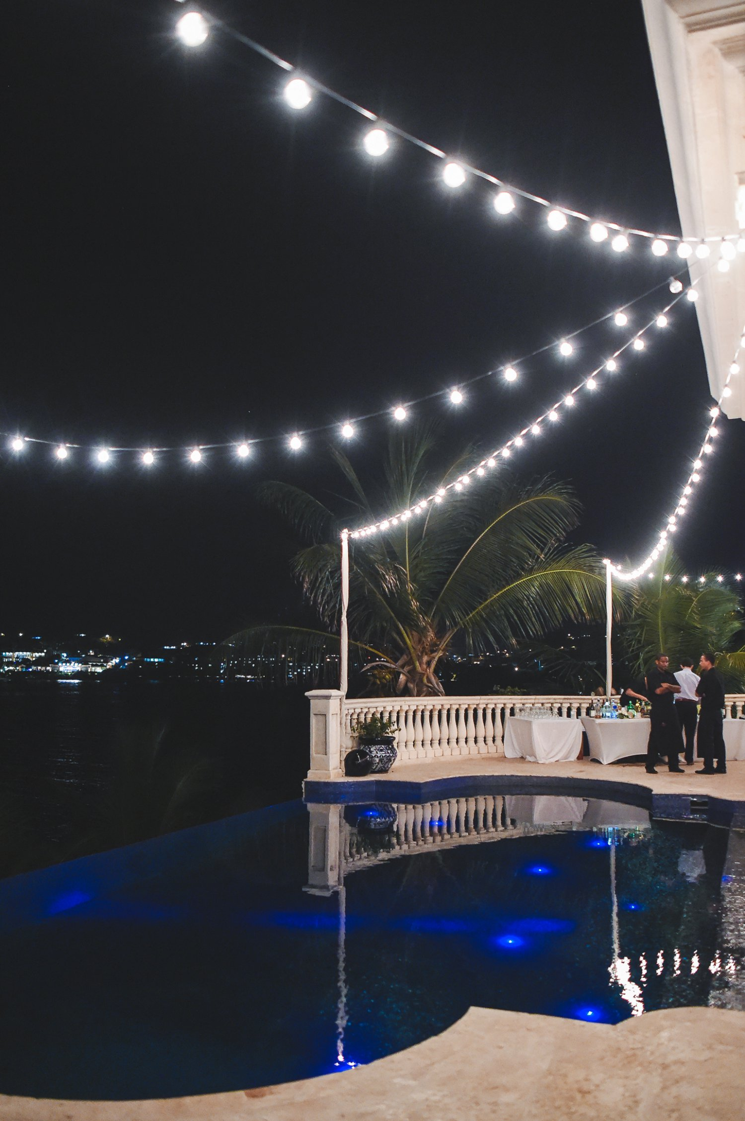 Bistro lights hung over pool in starburst pattern at private home reception venue in St. Thomas.