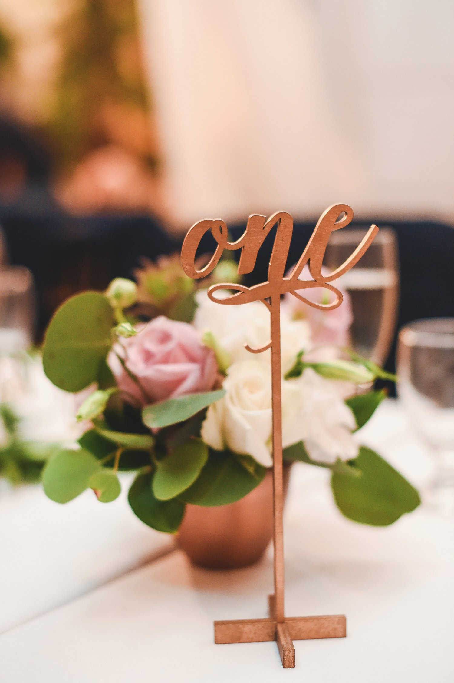 Scroll font cut out table numbers in gold.