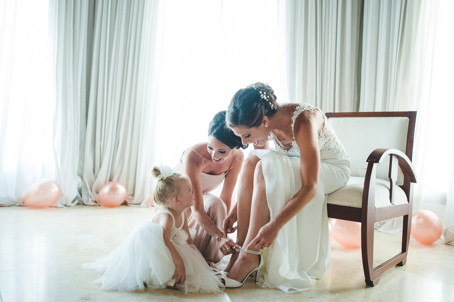 Bride gets ready and puts shoes on with flower girl on wedding day.