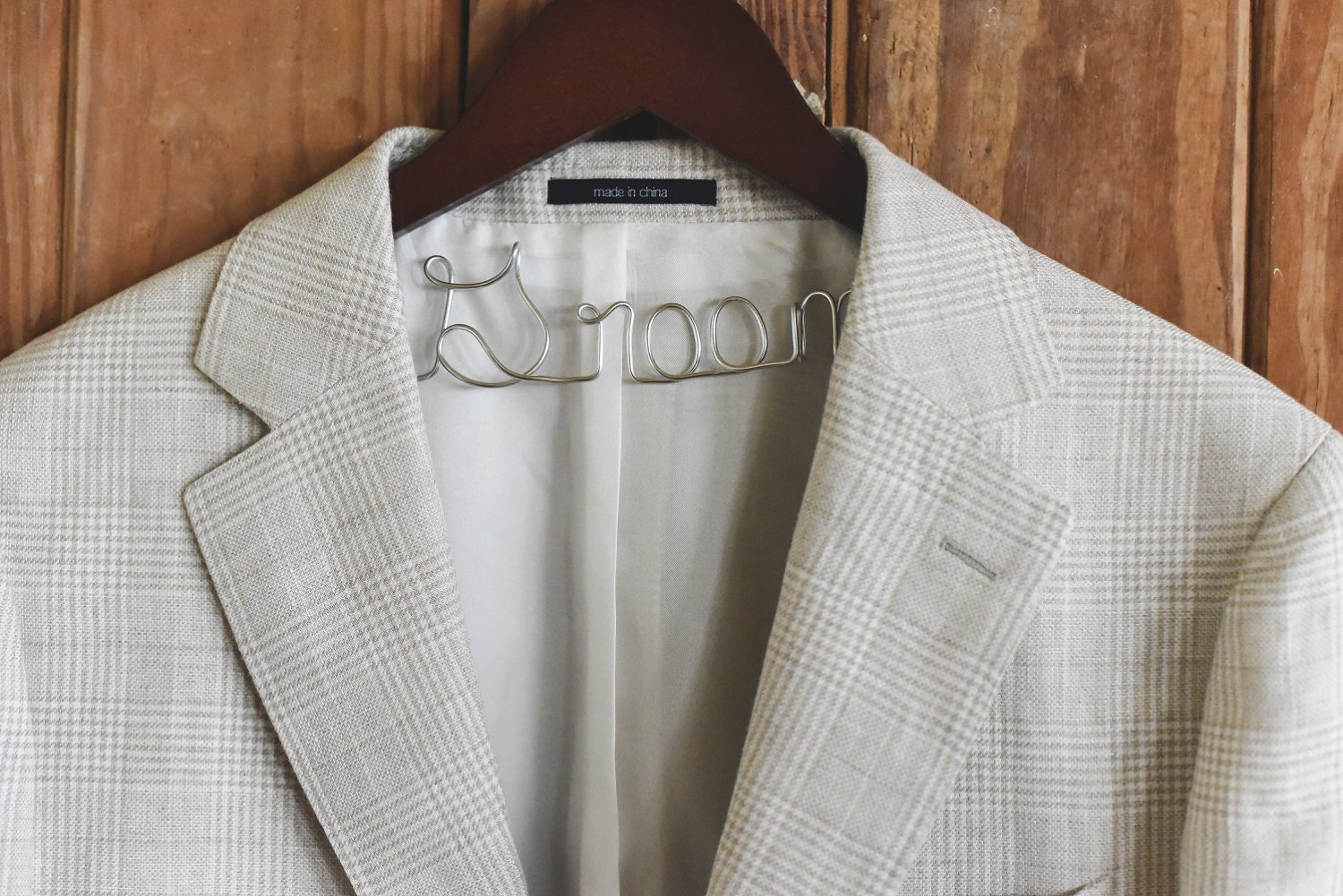 Custom decorative hanger to hold groom's suit jacket.