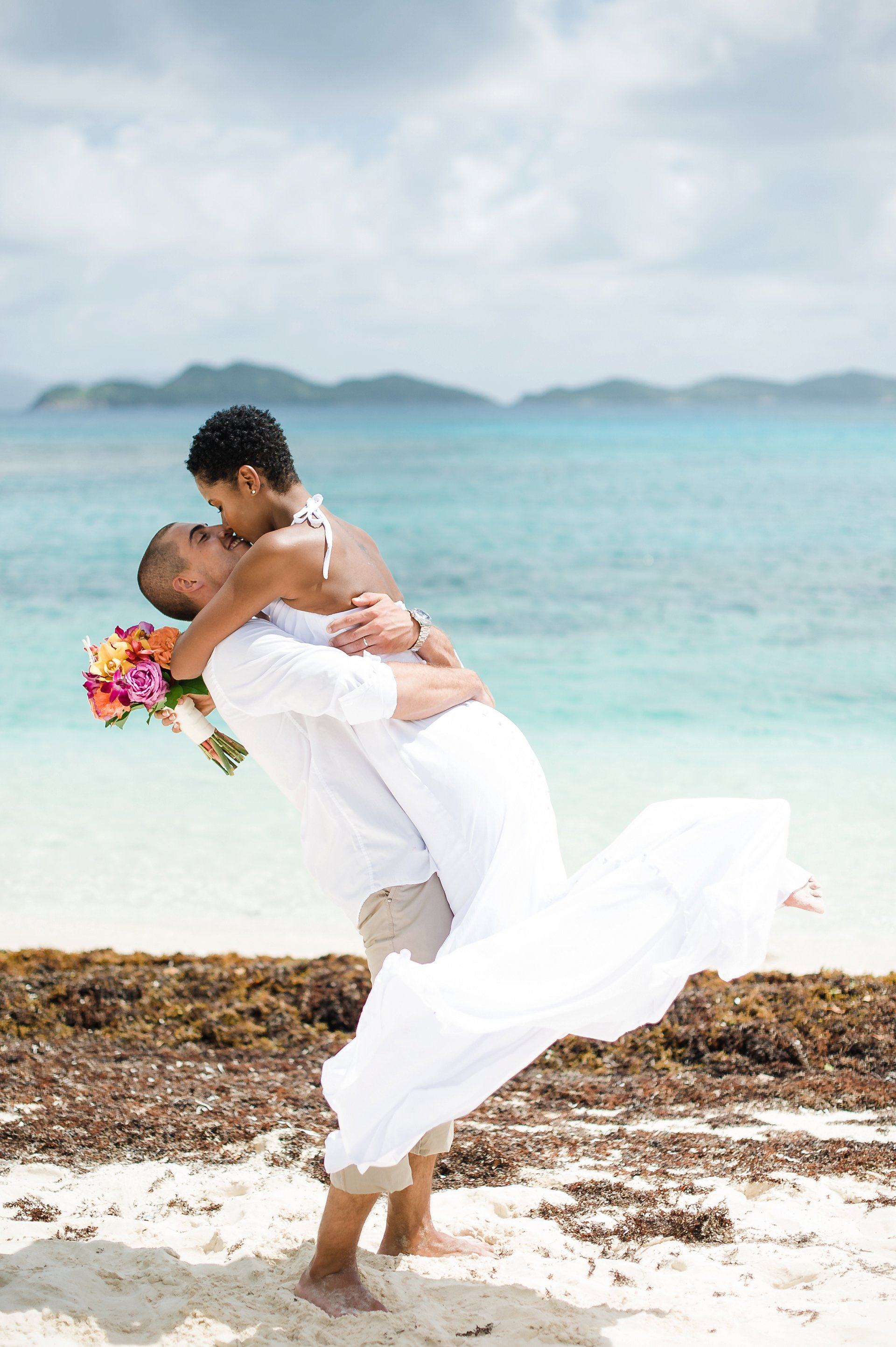 Must have beach wedding photo of groom lifting bride and kissing her.
