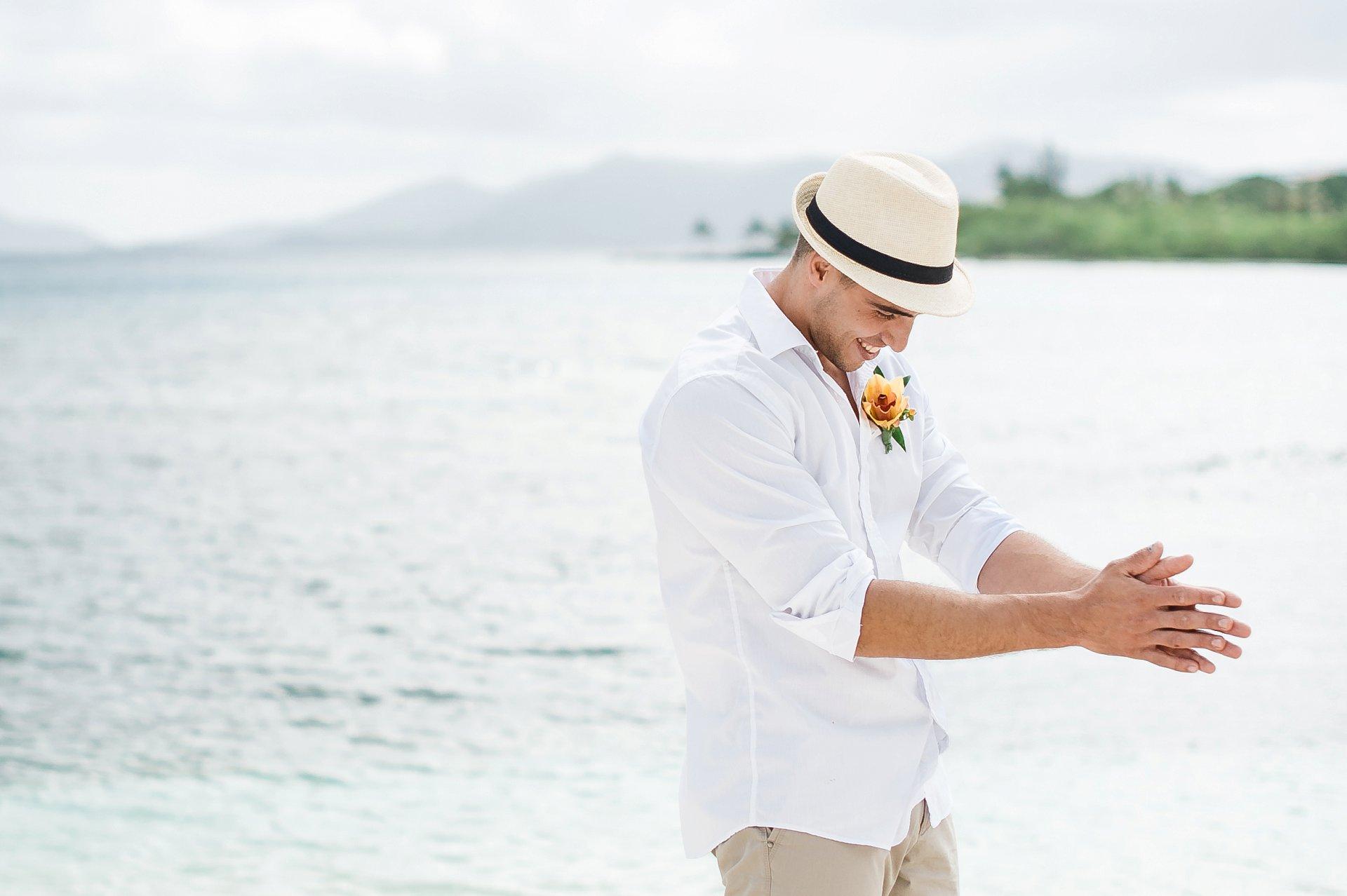Groom in straw fedora at beach wedding