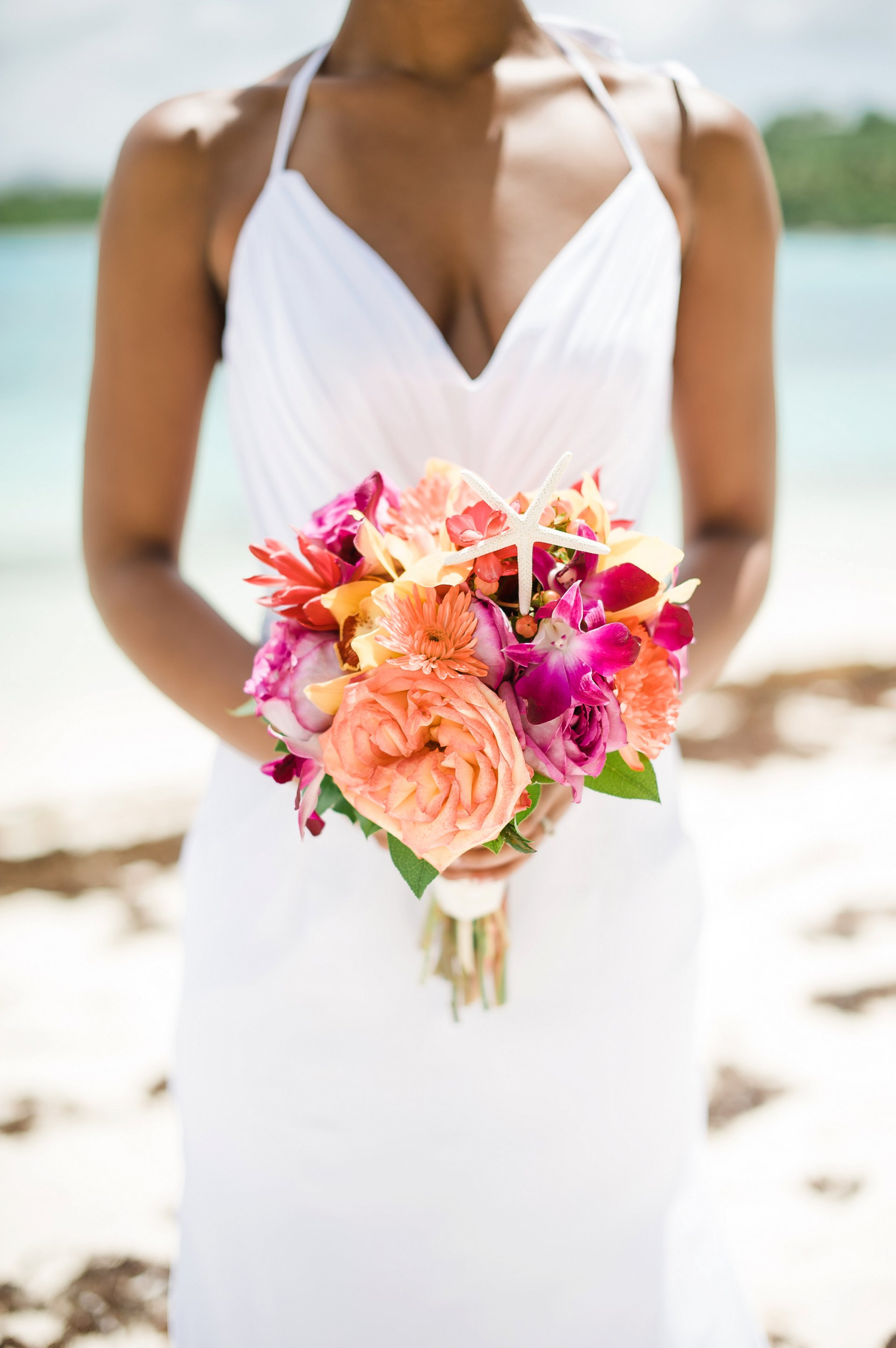 Orange and pink tropical bridal bouquet with starfish for a Caribbean destination wedding in St. Thomas.
