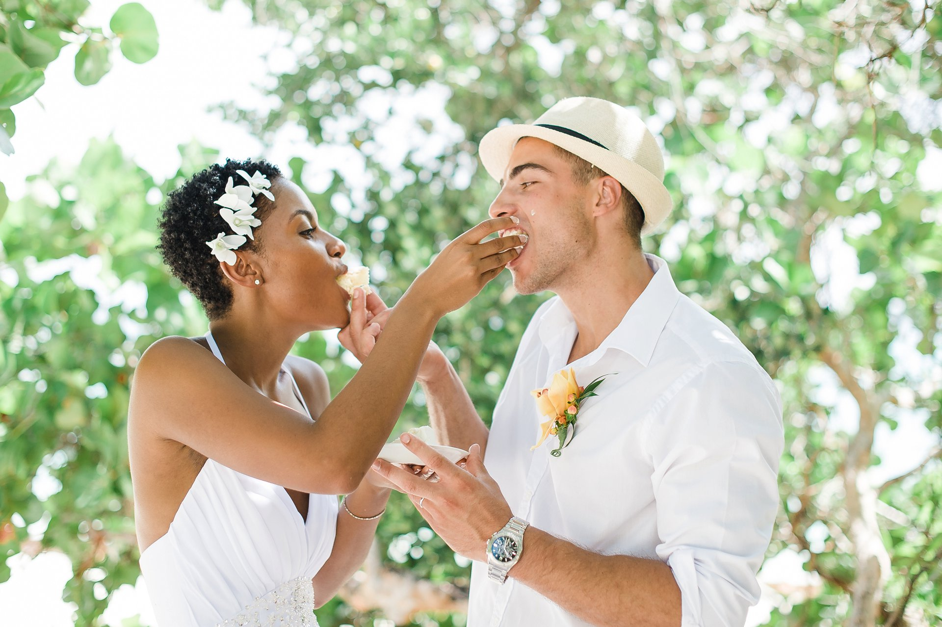 Couple feeds each other wedding cake at a tropical destination wedding.