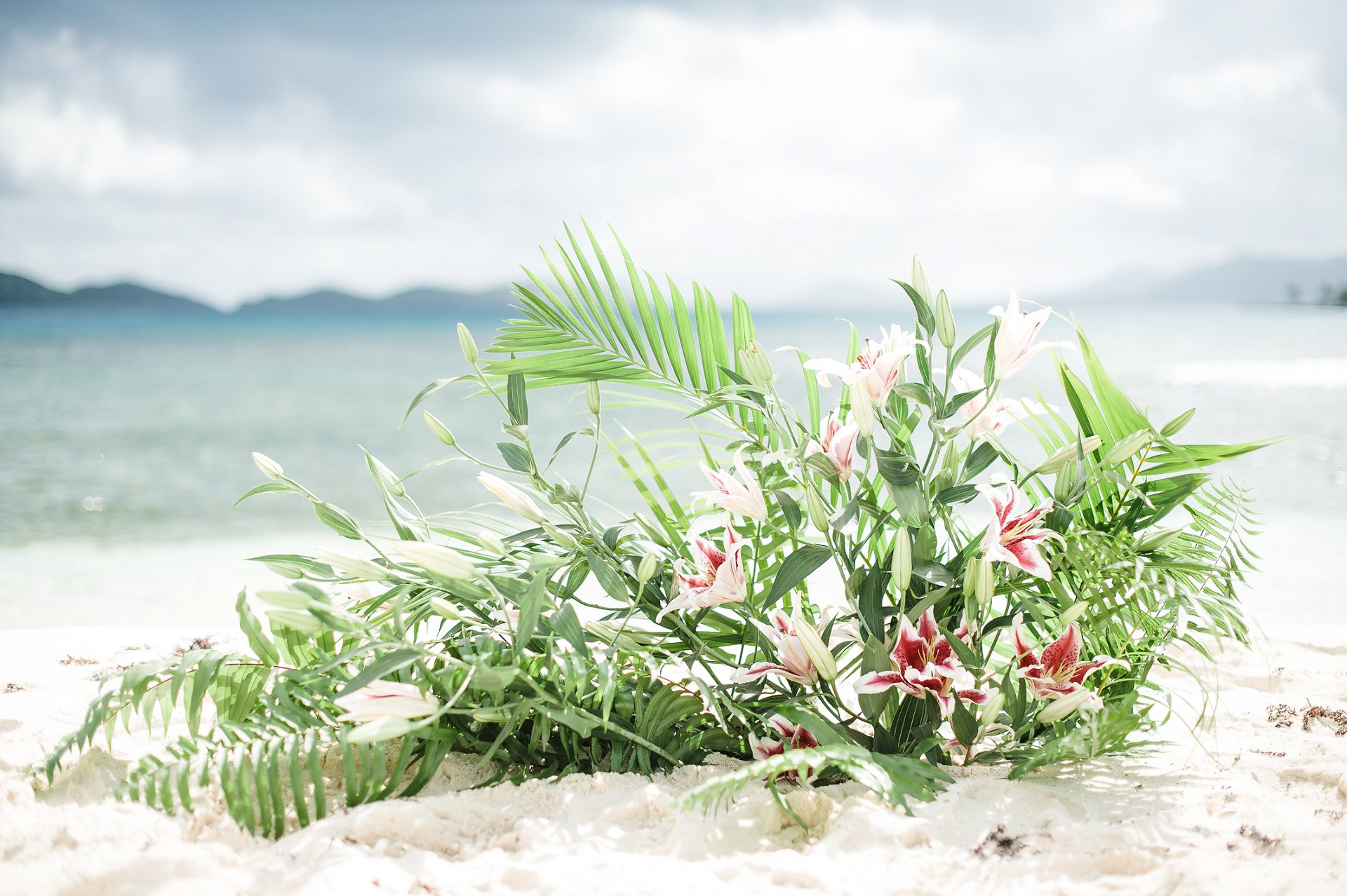 Tropical flowers, palms, ferns and lilies wedding altar for beach wedding in St. Thomas