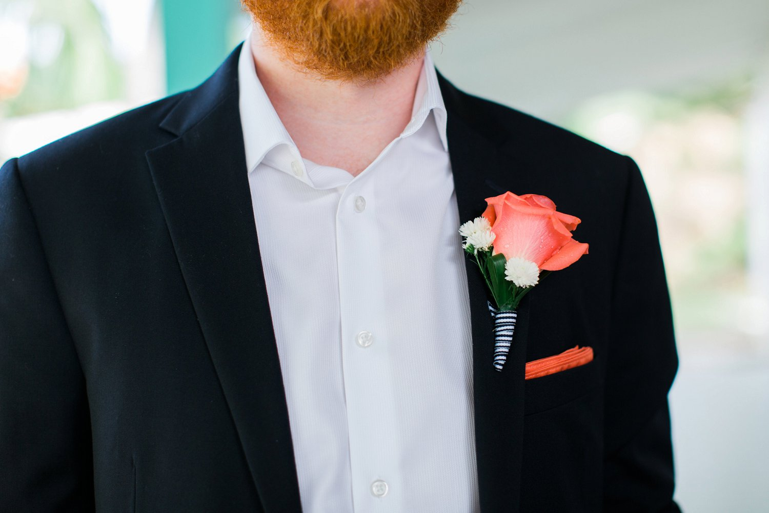 Coral boutonniere with blue and white striped ribbon and navy blue suit for groom for destination beach wedding.