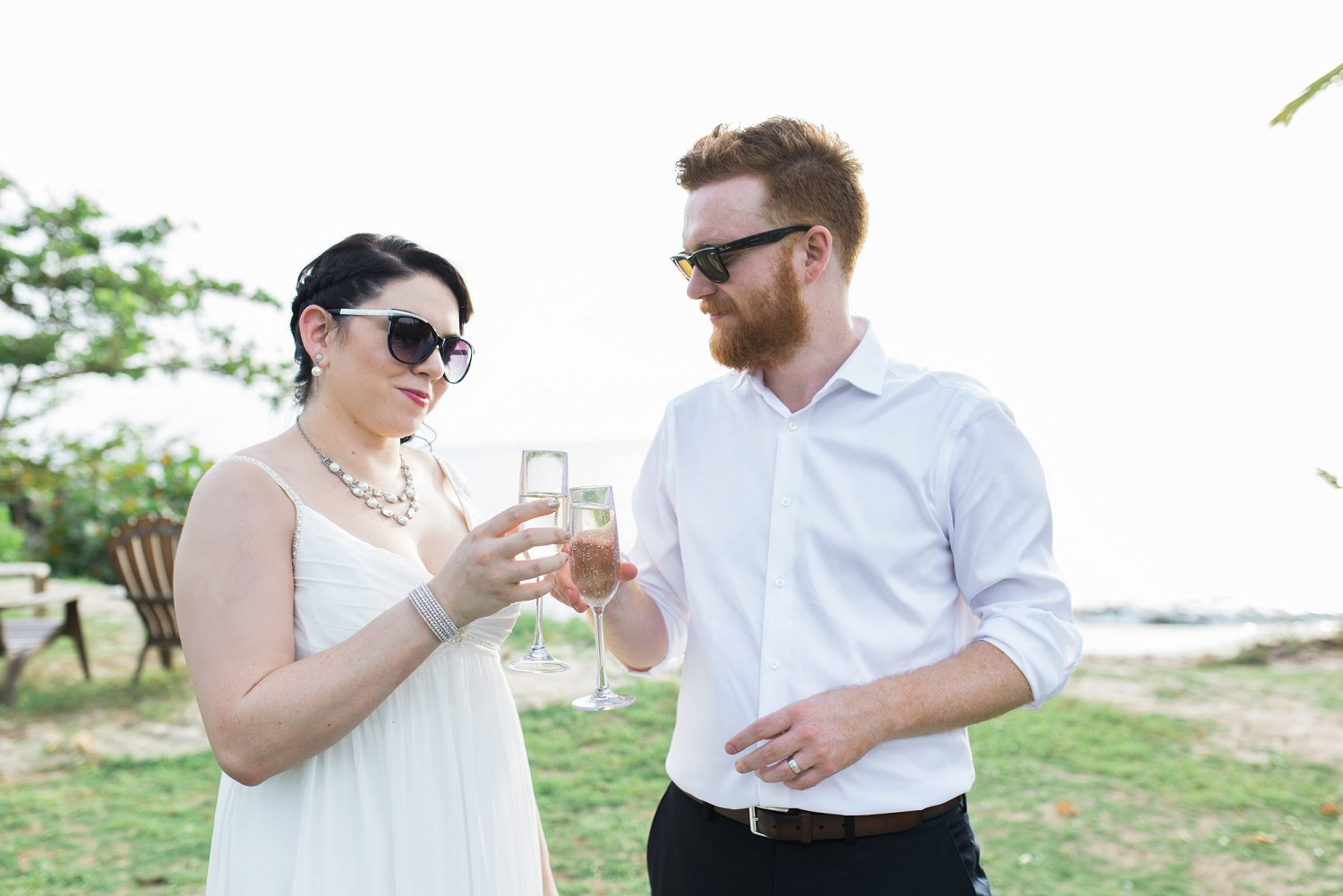 Couple toasts with champagne wearing sunglasses at beach wedding.