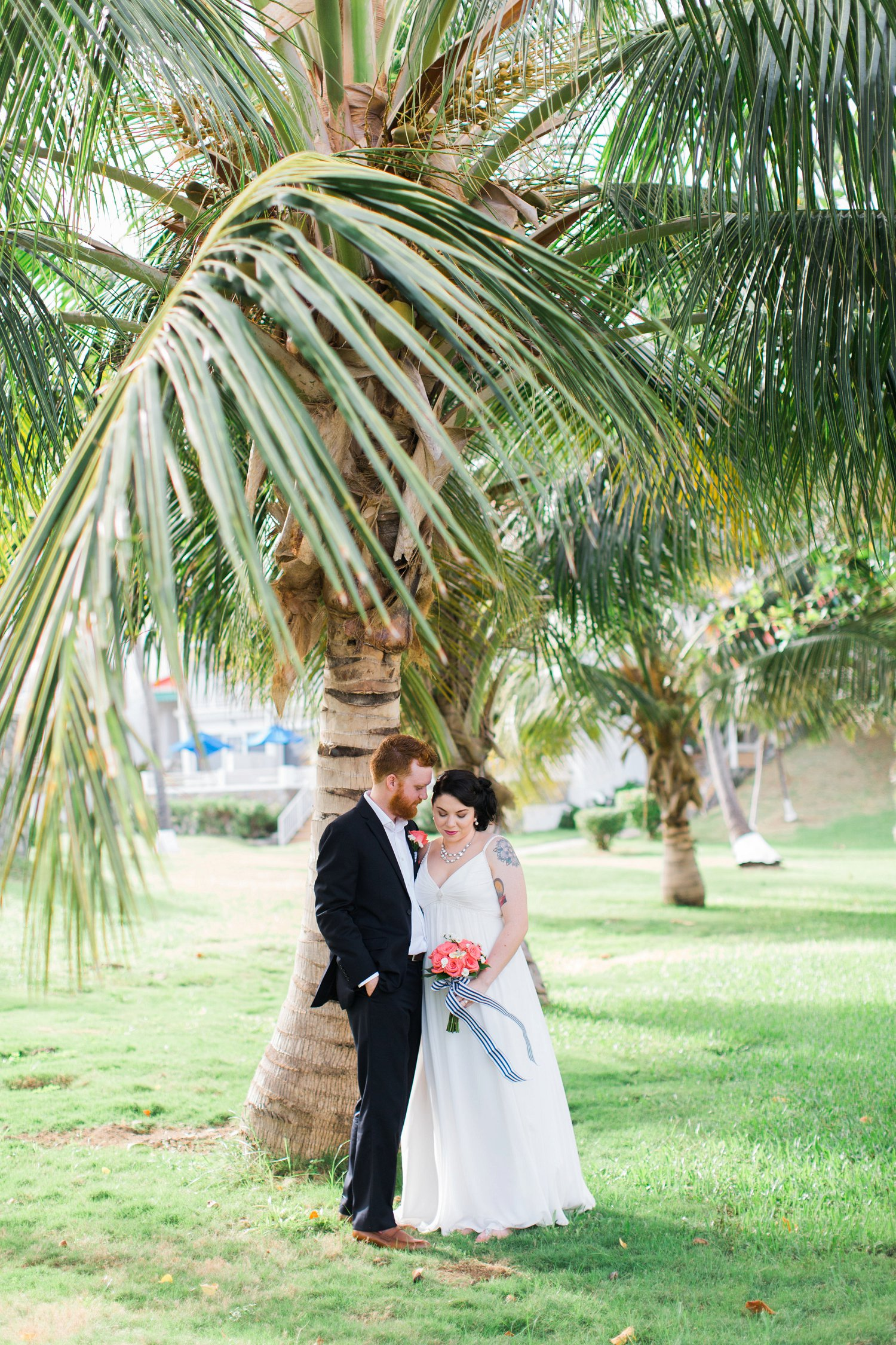 Bride and groom portrait under coconut palm tree at beach wedding in St. Thomas.