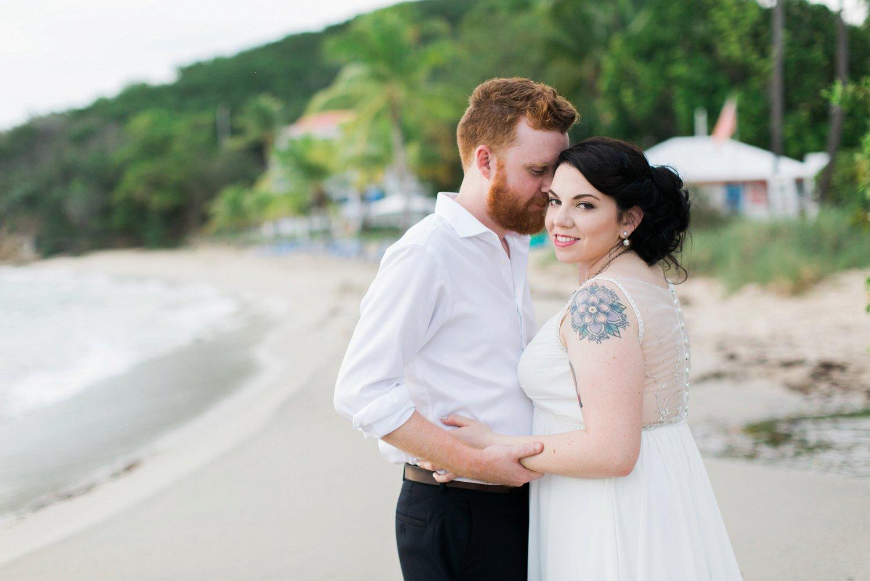 Groom kisses bride at Limetree beach, St. Thomas, USVI.