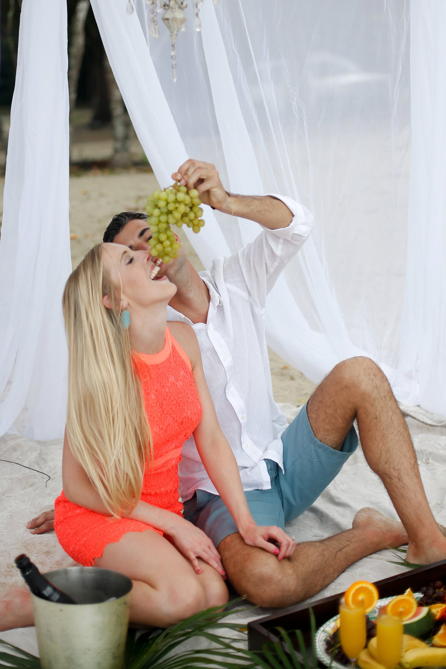 Fiance feeds fiance grapes at tropical themed engagement photography session.