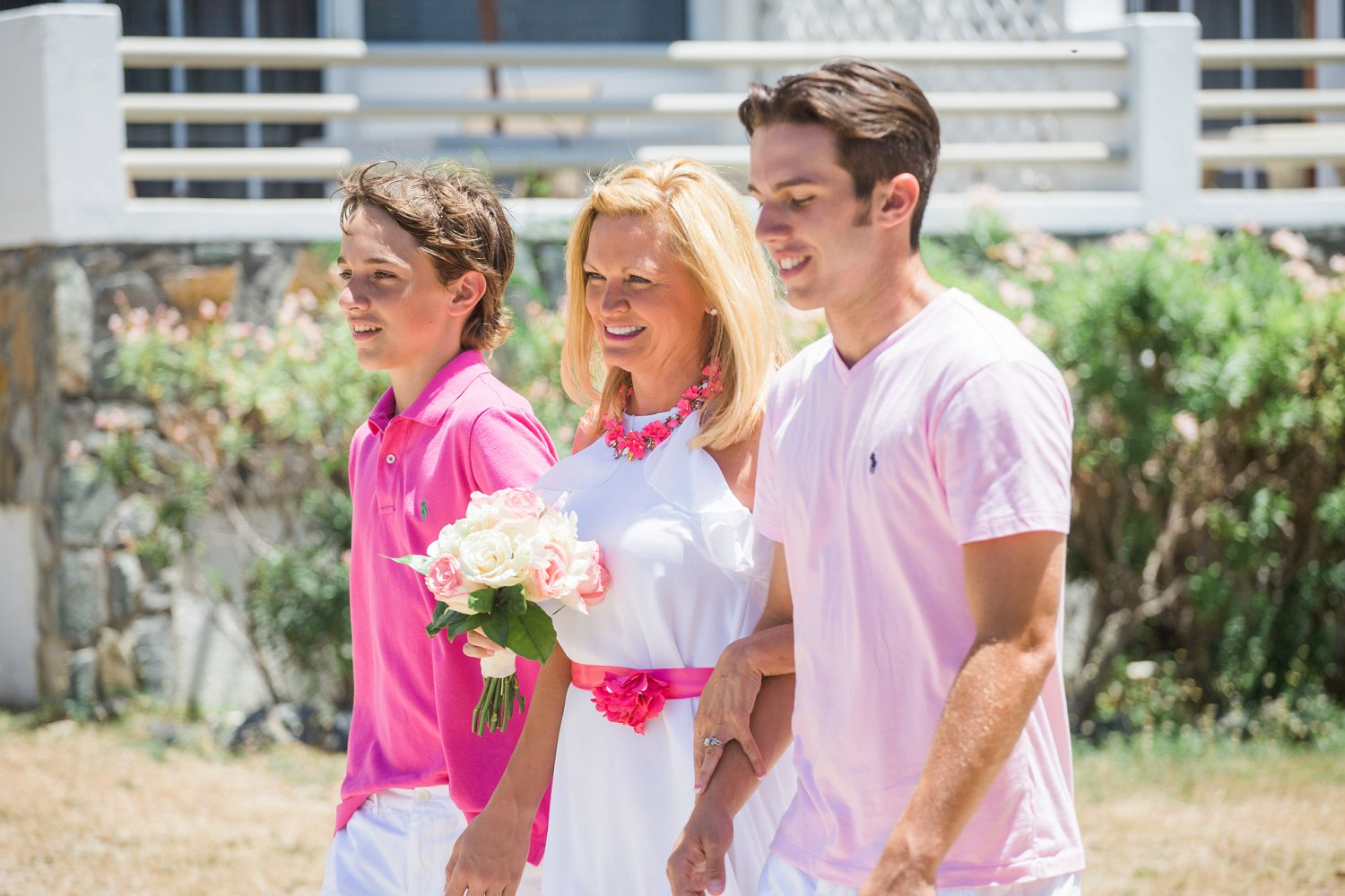 Wife walks down the aisle with sons at destination vow renewal ceremony.