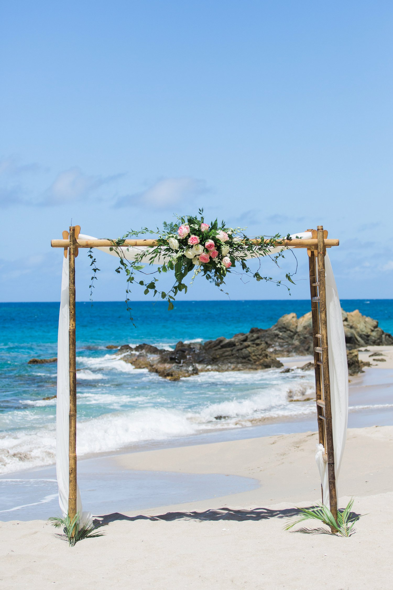 Wedding arch with pink, blush and white flowers and trailing greenery at Limetree beach.
