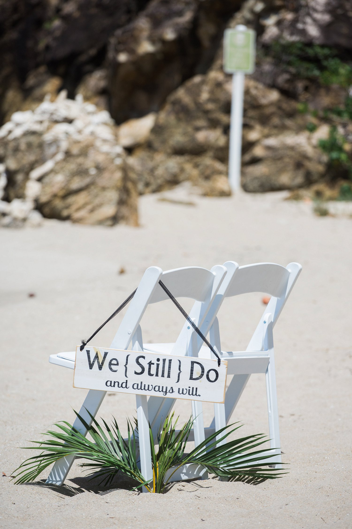 We still do vow renewal sign hangs from white garden chairs at beach ceremony in St. Thomas.