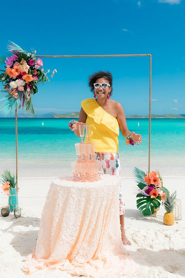 St. Thomas wedding Planner pours champagne with copper wedding arch background at destination elopement in St. Thomas