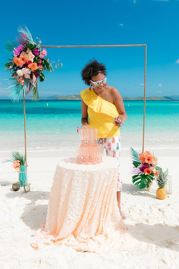 Wedding planner Amber Ambrose pours champagne at destination wedding at Lindquist Beach, St. Thomas