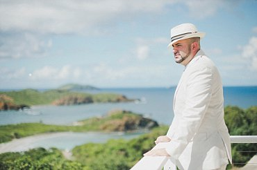 Groom in hat admires tropical view.