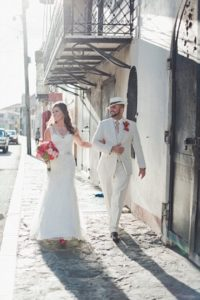 Bride and groom stroll through downtown Charlotte Amalie, St. Thomas after catholic church wedding