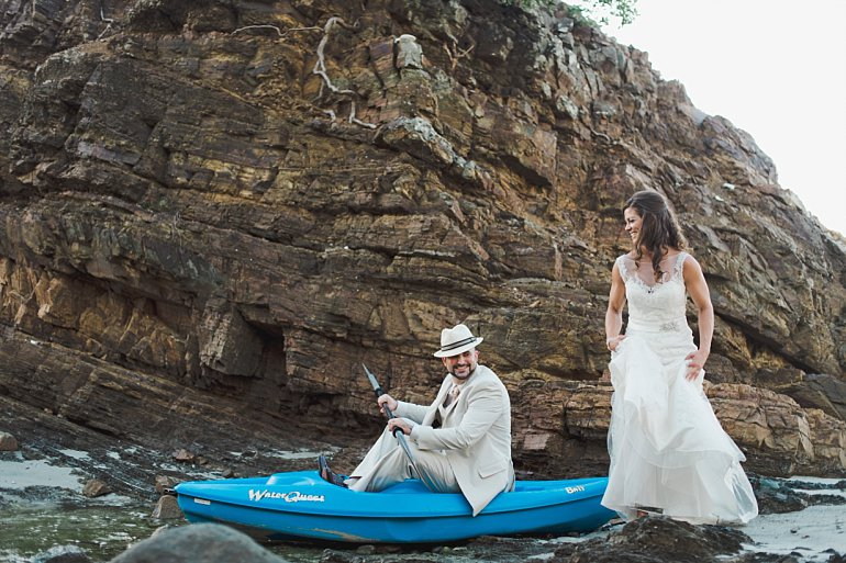 Bride and groom pose for wedding portrait in kayak