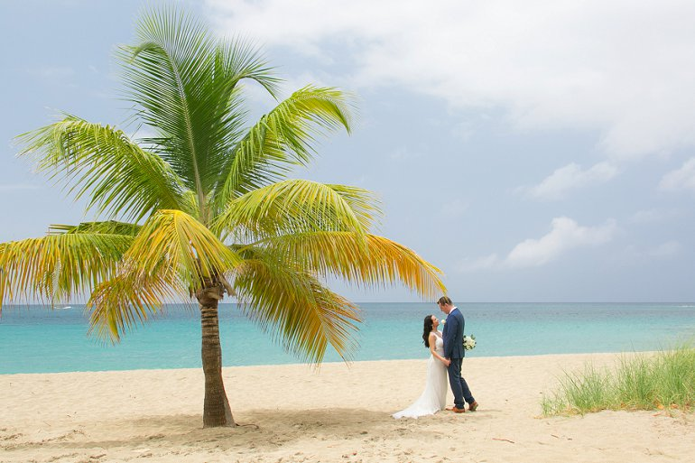Bride and groom kissing under coconut palm tree in St. Thomas