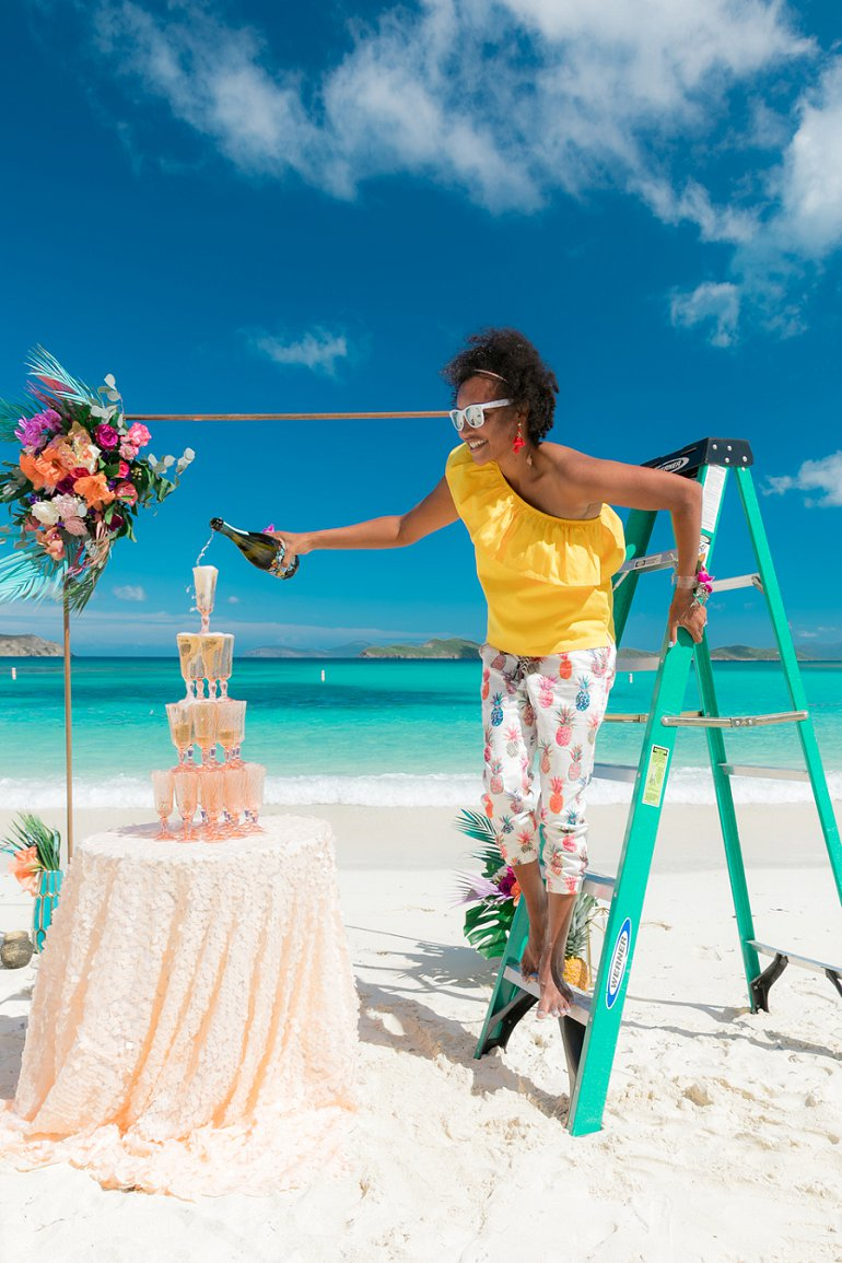 St. Thomas wedding planner Amber Ambrose of Blue Sky Ceremony pours champagne on Lindquist Beach