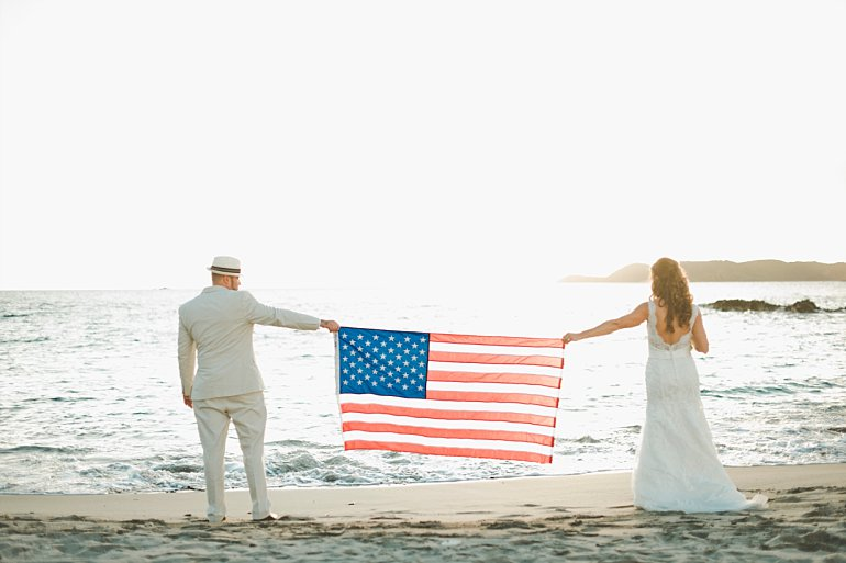 Couple poses for wedding photo with American flag on St. Thomas beach