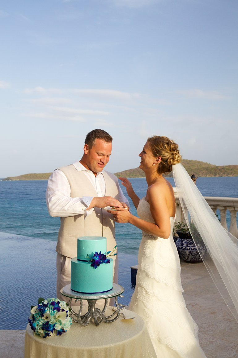 Cake cutting a St. Thomas destnation wedding with aqual blue 2 tiered cake with blue galaxy orchids