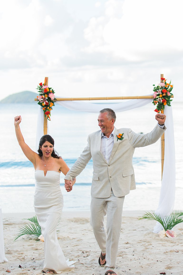 Happy bride and groom walk back up aisle after destination wedding in St. Thomas with wedding planning package from Blue Sky Ceremony