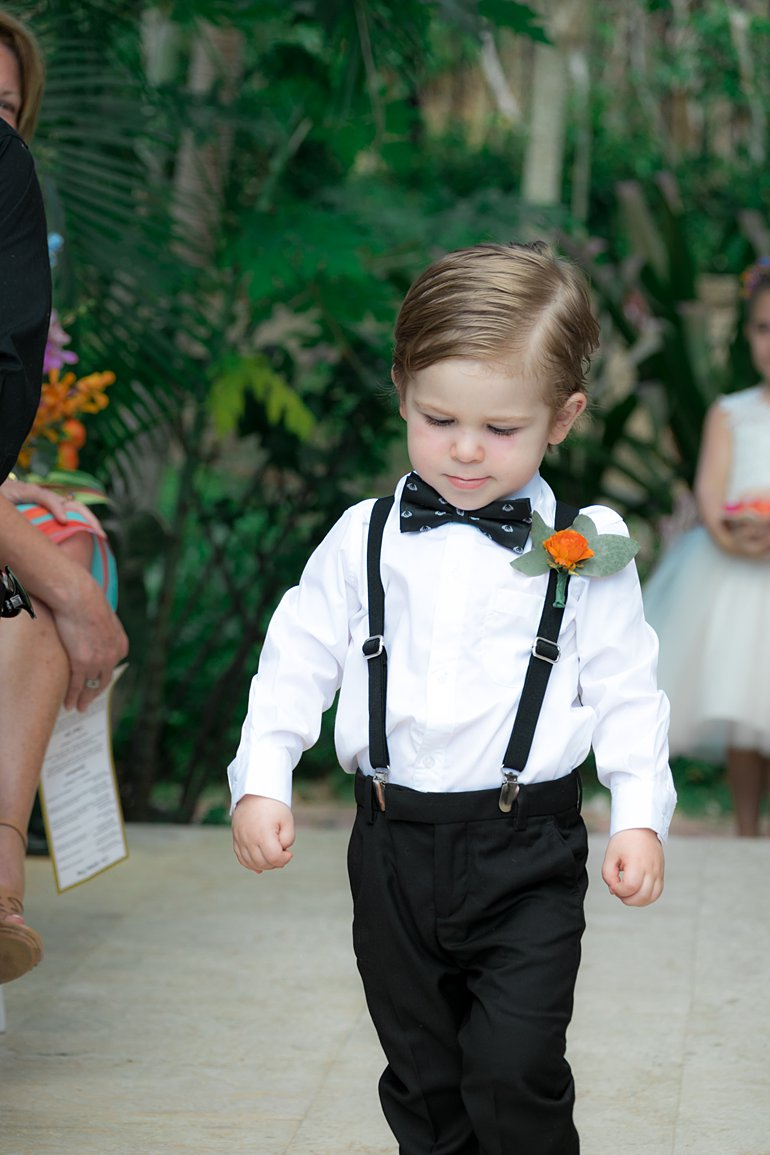 Ringbearer with black bowtie and suspenders and boutonniere