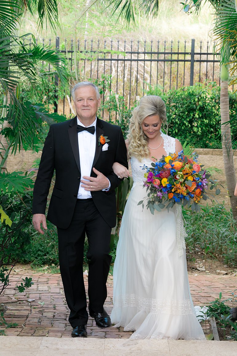 Bride in vintage lace wedding gown with large, colorful bouquet is escorted by her father wearing a tux tuxedo.