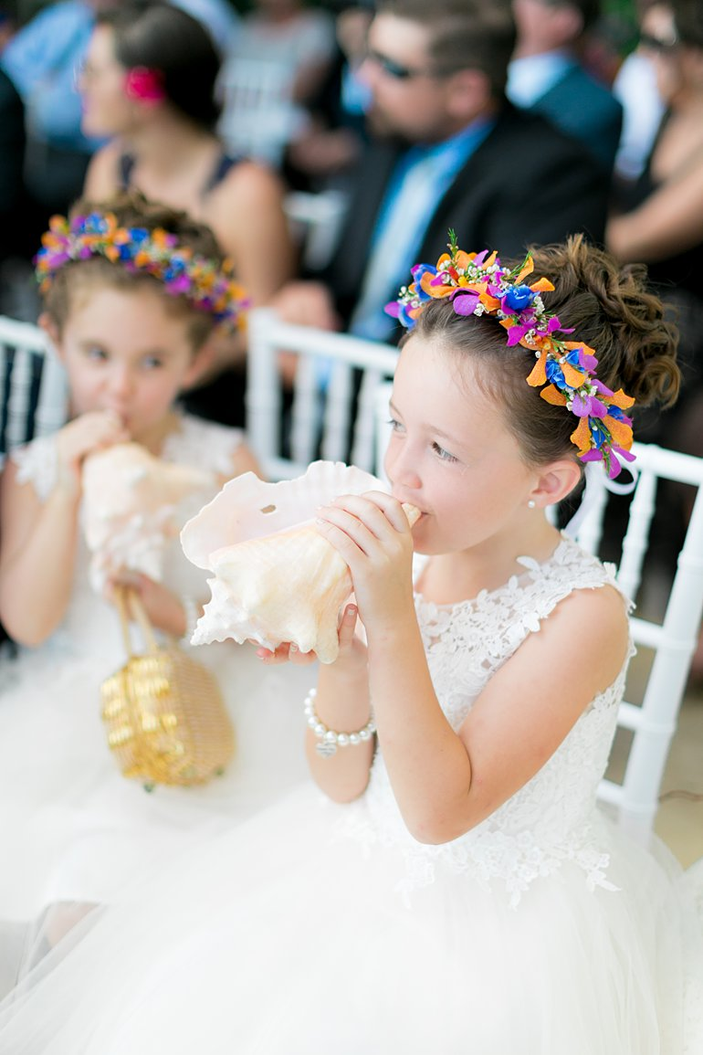 Flower girls with tropical floral crown halos blow conch shells at destination wedding in St. Thomas