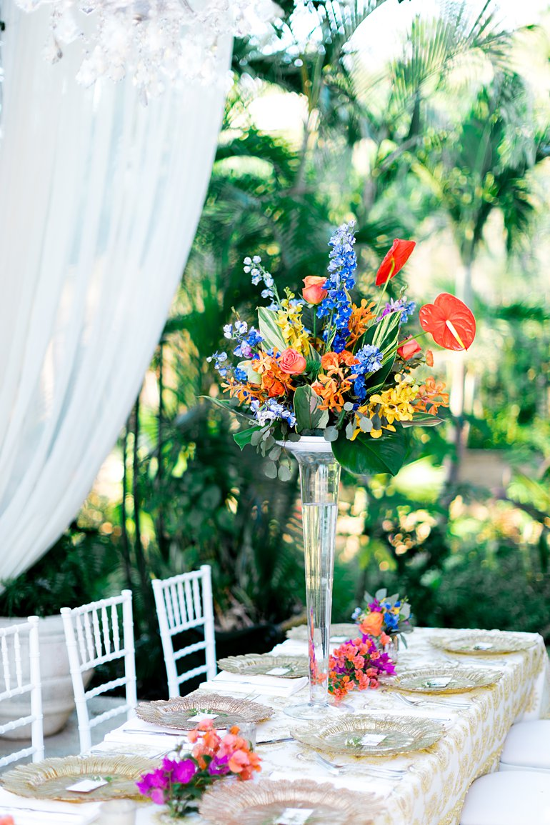 Tall tropical colored centerpieces with gold chargers.