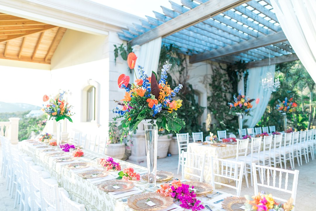 Elegant tropical wedding reception decorations at private villa reception in St. Thomas with tall centerpieces.