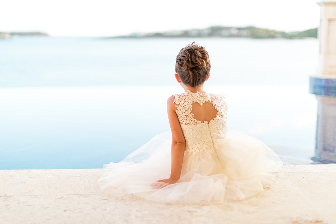 Flower girl with lace and chiffon dress sits with her feet in pool at destination wedding in St. Thomas at Villa Serenita.