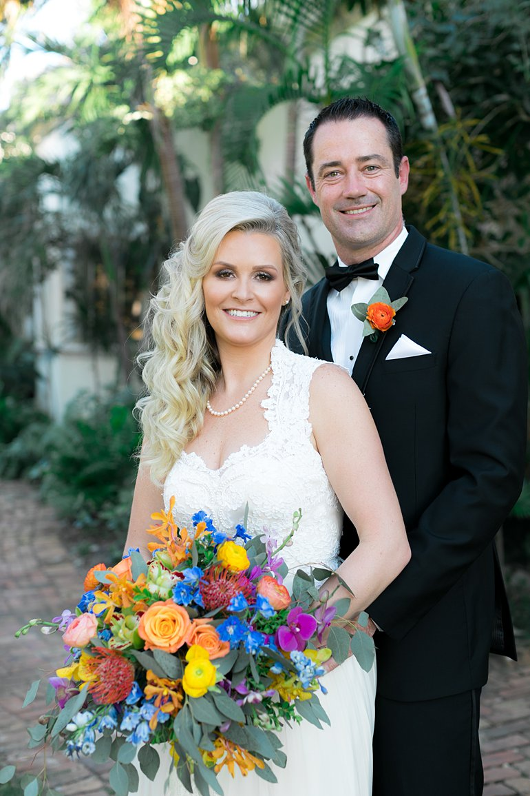 Couple poses at formal destination wedding with giant colorful bouquet, tuxedo and vintage lace wedding gown.