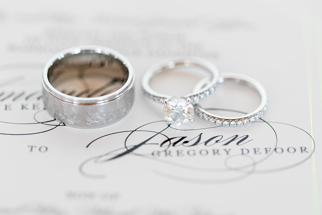 Close up photo of wedding bands and engagement ring on top of wedding invitation.