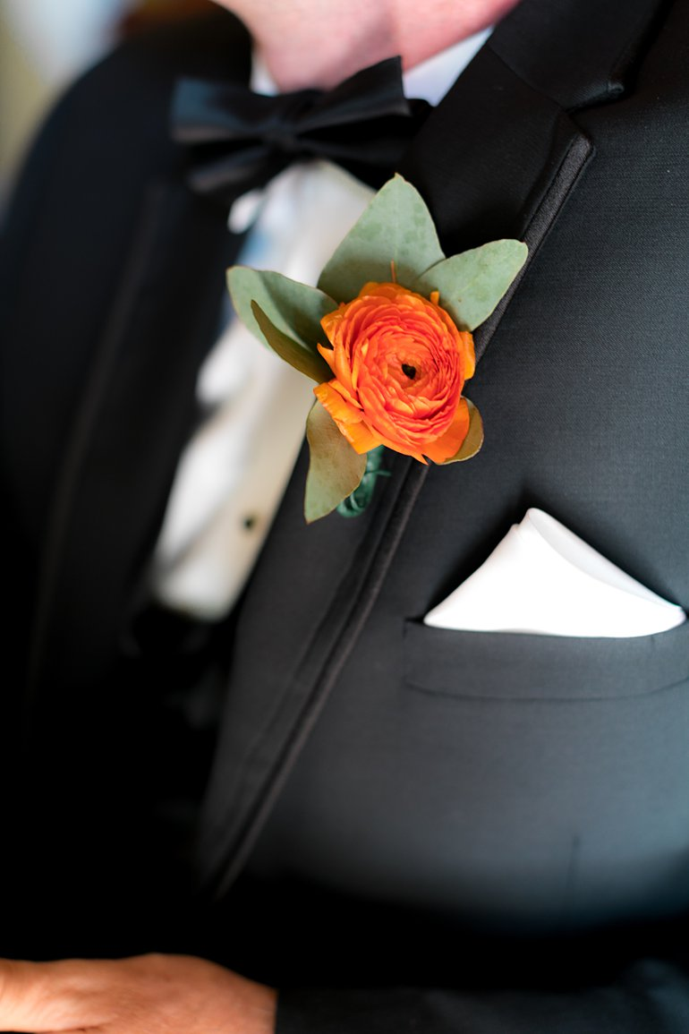 Close up photo of orange ranunculus  boutonniere with black tuxedo