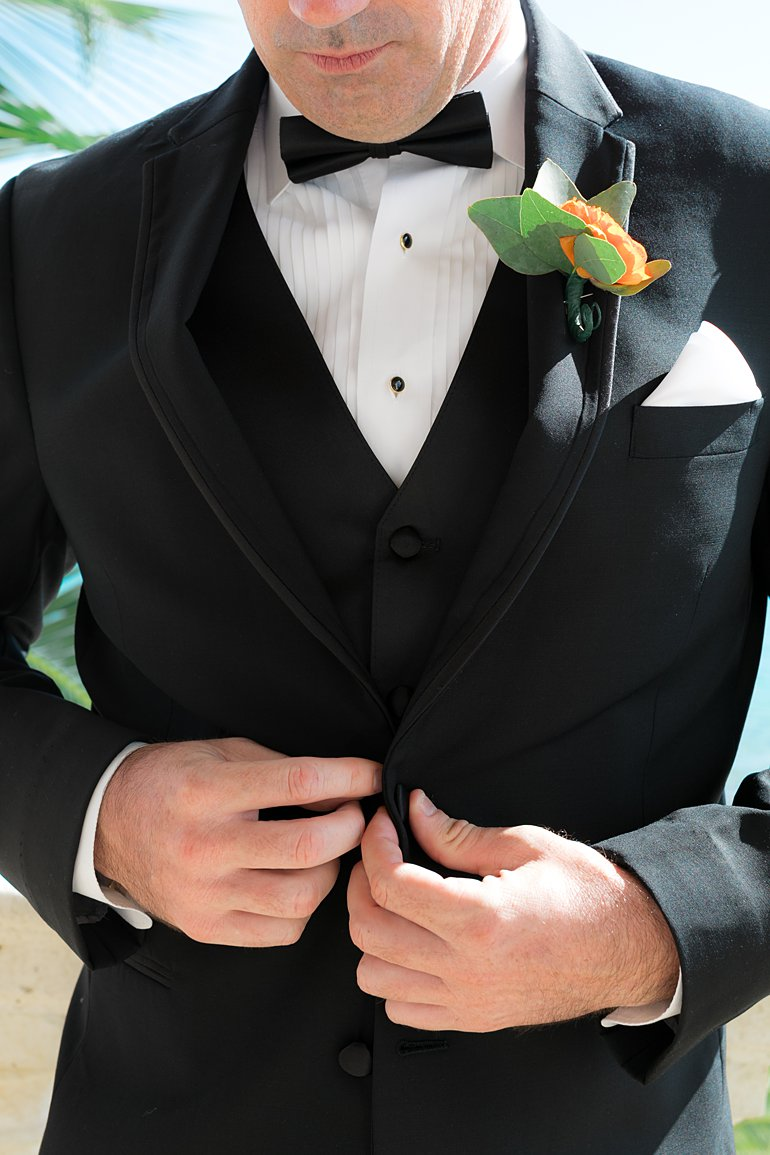 Groom buttons black tux at destination wedding