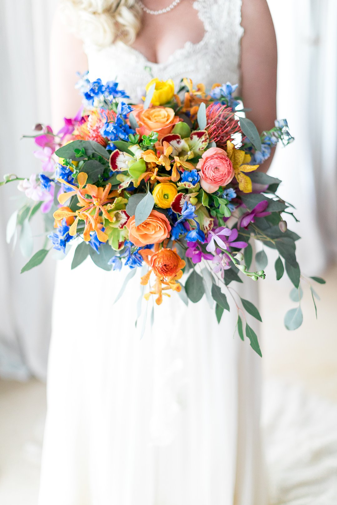 Bride poses with the biggest oversized bridal bouquet with tropical colors and tropical orchids, pin cushion and ranunculus flowers with blue flowers.