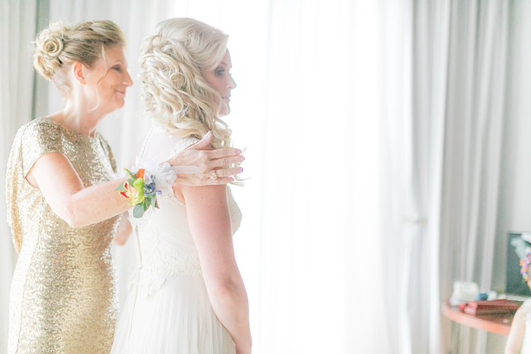 Bride and her mother get dressed for wedding