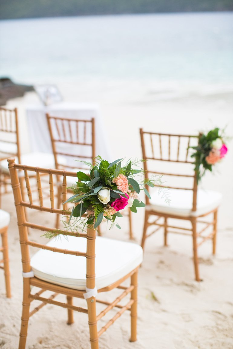 Chiavari chairs with floral adornment for beach wedding ceremony set up at Sand Dollar Estate private beach in St. Thomas, Virgin Islands