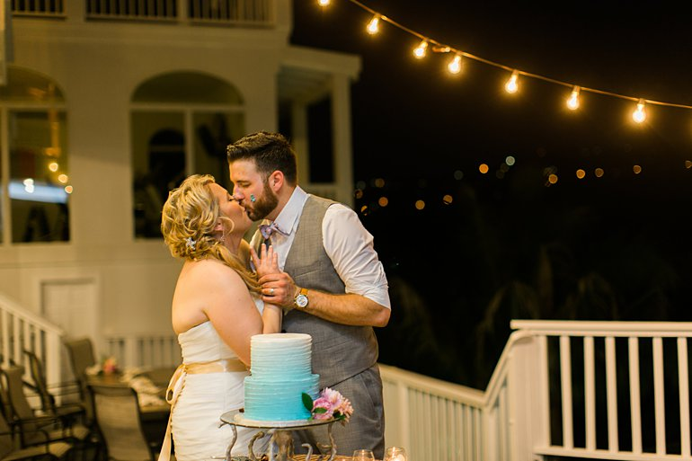 Bride and groom kiss after cutting wedding cake at Sand Dollar Estate.