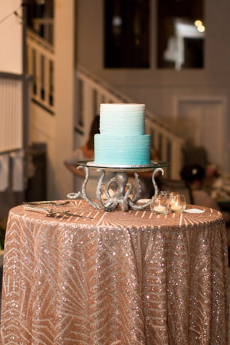 Blue ombre wedding cake on rose gold sequined tablecloth table for beach themed destination wedding