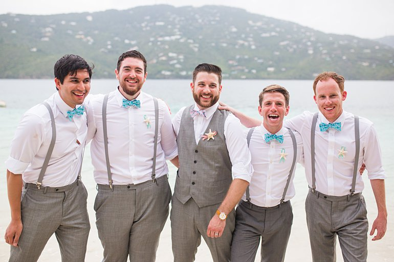 Groom and groomsmen wearing gray suit pants with suspenders, vest and aqua/turquoise blue bow ties for beach wedding attire.