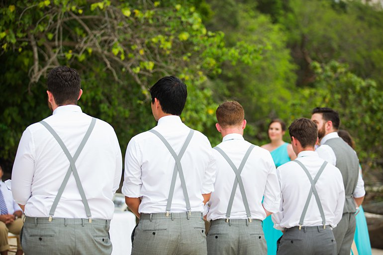 Groomsmen wearing gray suspenders and gray slacks at beach wedding in St. Thomas